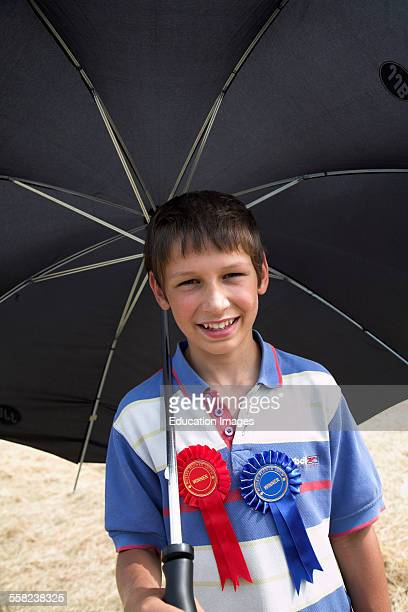 Red and blue winner badges on a boys chest as he holds a big black umbrella Butley Suffolk England