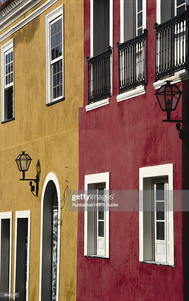 red and dark yellow stucco homes with white framing around windows and doorways in Europe : Foto de stock