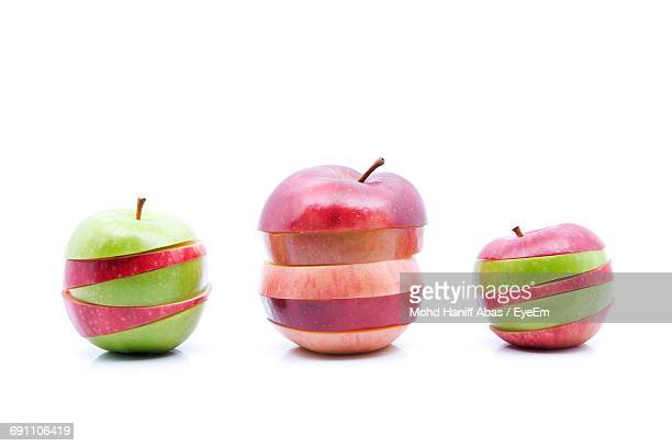 Red And Green Apple Slices Over White Background