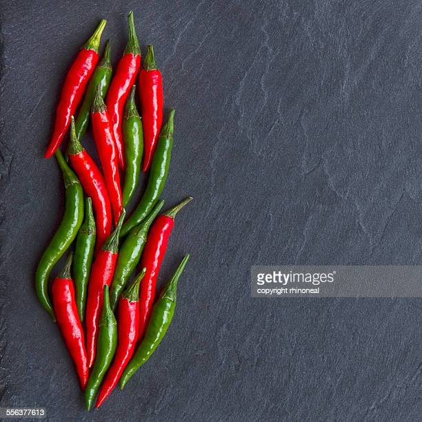 Red and green chillies on slate