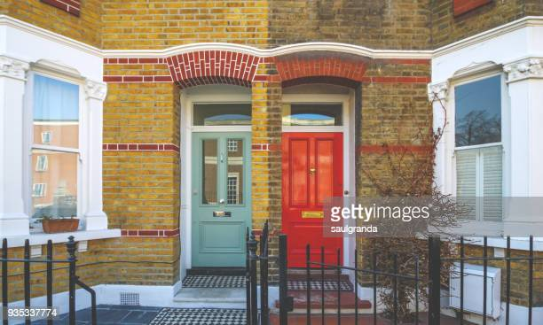 red and green doors on a brick facade - english culture stock pictures, royalty-free photos & images