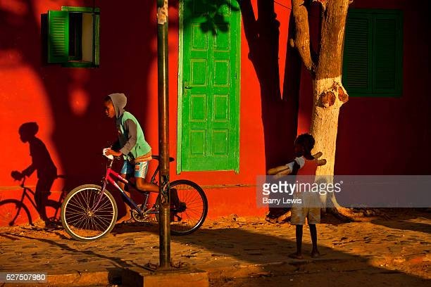 Red and green in a colourful street scene passing homes on Goree island Senegal Gor��e is both the smallest and the least populated of the 19...