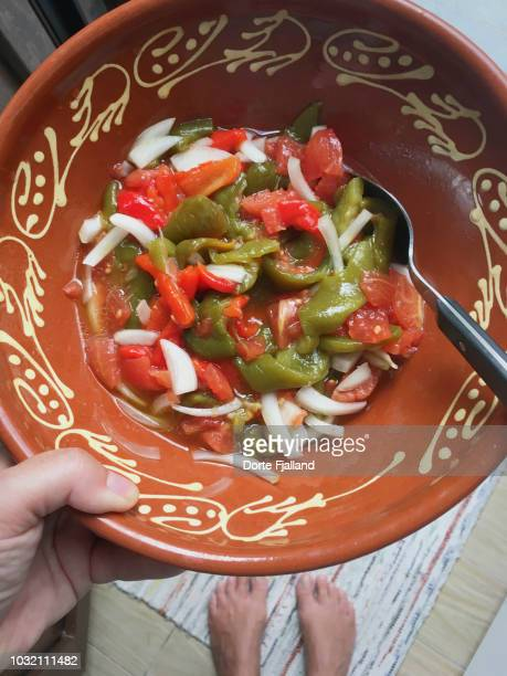 Red and green pepper salad in a brown clay bowl held in one hand
