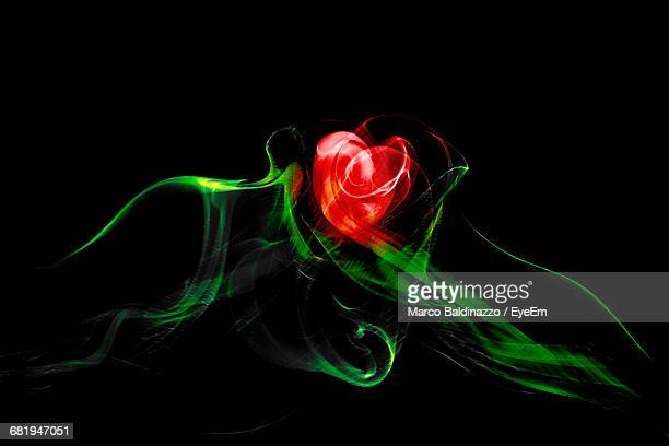 Red And Green Smoke Making Rose Against Black Background