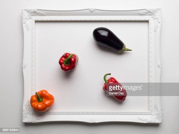 Red and orange peppers and an aubergine colourfully displayed within a white picture frame on a white background