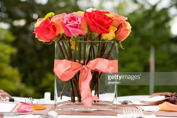 Vermelho e laranja de rosas em jarra de vidro na tabela