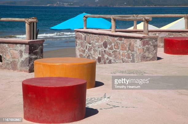 red and orange round benches on a patio in foreground; beach umbrellas and ocean beyond; tenacatita bay, costalegre, jalisco, mexico - timothy hearsum stock-fotos und bilder