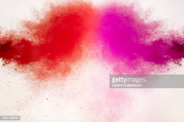 Red and pink Holi colors splashing over white background