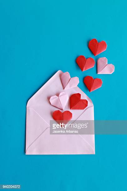 red and pink paper hearts on the pink envelope - valentines day fotografías e imágenes de stock