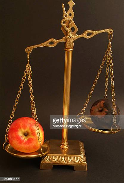 Red and rotten apple on a scale