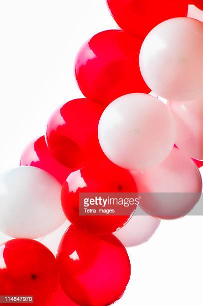 Red and white balloons on white background, studio shot