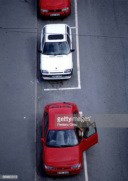 Red and white cars parked on asphalt,  birdseye view.