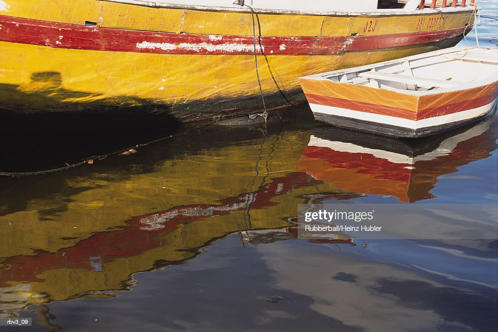 red and white fishing boats reflect in water in a European harbor : Foto de stock