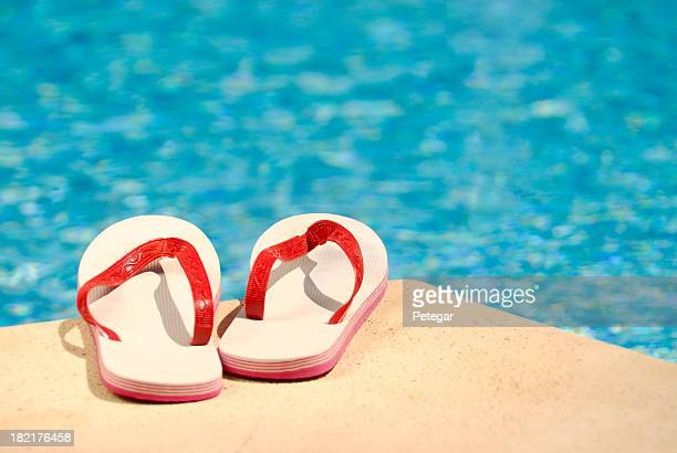 Red and white flip flops on pools edge