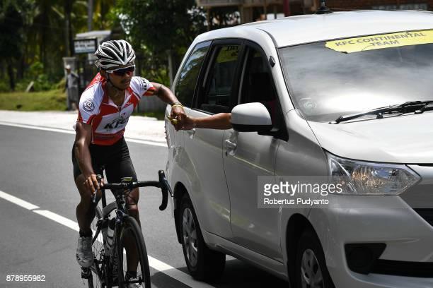 Red and White jersey winner Jamal Hibatullah of KFC Cycling Team Indonesia grabs a banana during stage 8 of the Tour de Singkarak 2017 Padang...