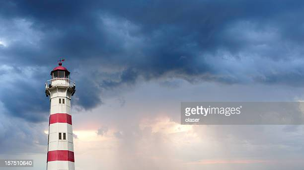 Red and white lighthouse against dramatic sky