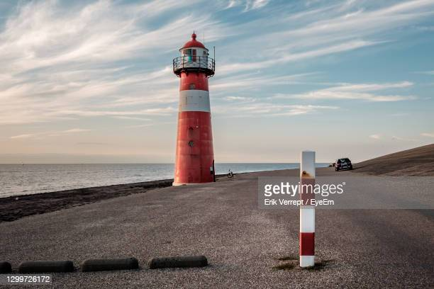 red and white lighthouse by sea against sunset sky - middelburg netherlands stock pictures, royalty-free photos & images