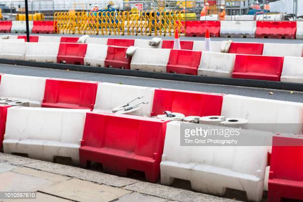 red and white plastic barriers on a road - construction barrier stock pictures, royalty-free photos & images