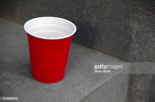 red and white plastic cup on an inner city doorstep - disposable cup stock pictures, royalty-free photos & images