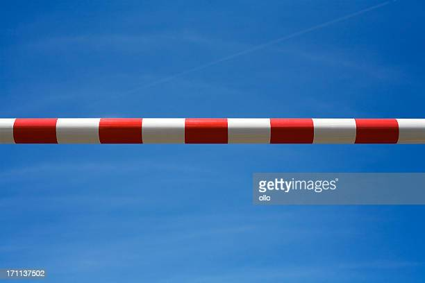 Red and white road barrier against blue sky