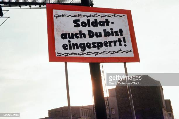 Red and white sign with barbed wire graphic on the border between West Berlin and East Berlin during the Cold War with text in German reading Soldat...