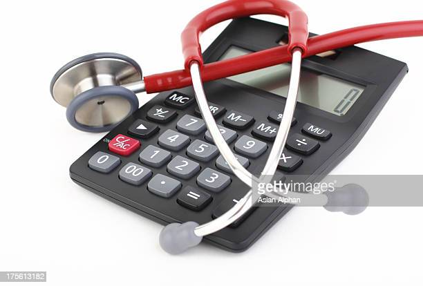Red and white stethoscope on top of a black calculator