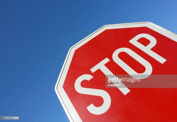 Red and white stop sign from low view