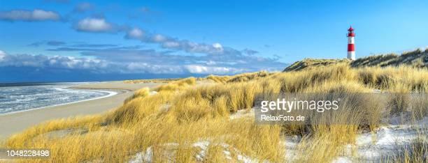 rot-weiß gestreifte leuchtturm auf sanddünen der insel sylt im winter - meerlandschaft stock-fotos und bilder