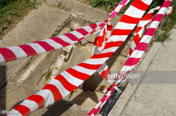 Red and white striped plastic cordon tape around a utility access point with a broken cement cover