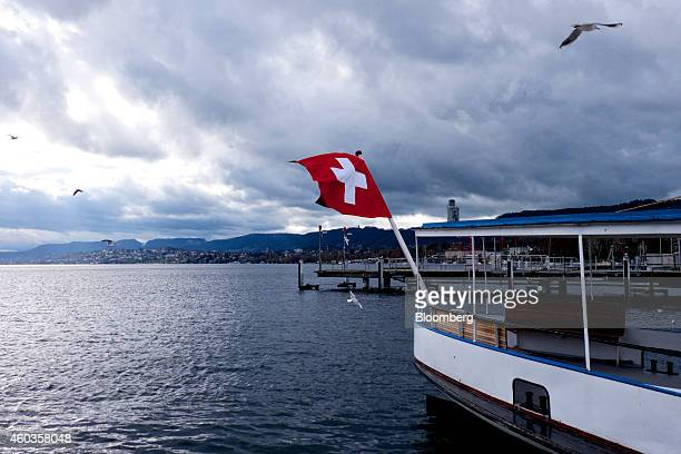 A red and white Swiss national flag flies from the stern of an empty pleasure boat moored to the quay on Lake Zurich in Zurich Switzerland on...
