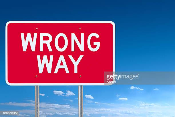 red and white wrong way road sign post over sky - wrong way stock pictures, royalty-free photos & images