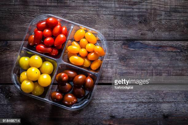 Tomates cherry rojos y amarillos en la rústica mesa de madera