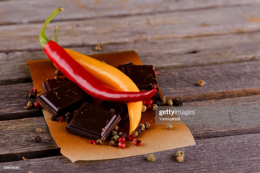 Red and yellow chili peppers with dark chocolate : Stockfoto