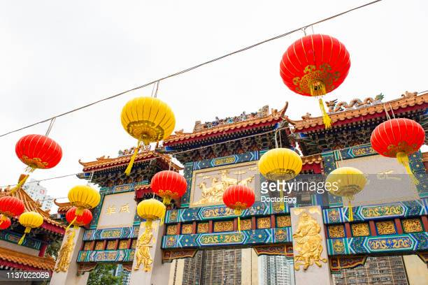 red and yellow lanterns in front of wong tai sin temple, kowloon - hong kong stock pictures, royalty-free photos & images