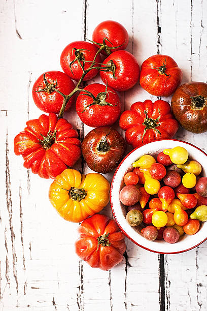 Red and yellow tomatoes on white table