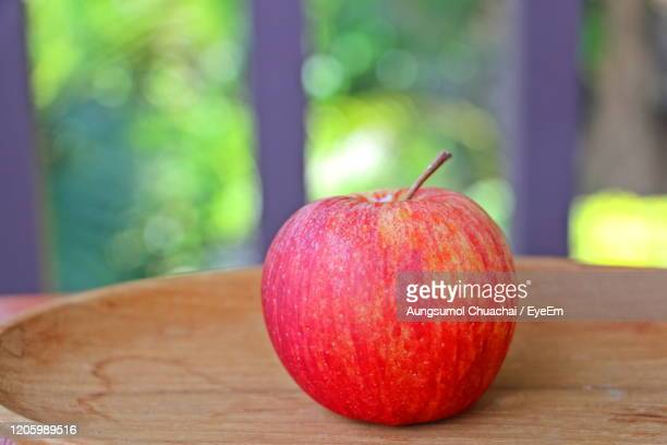 a red apple on the wooden plate with blur background. food concept. - aungsumol stock pictures, royalty-free photos & images