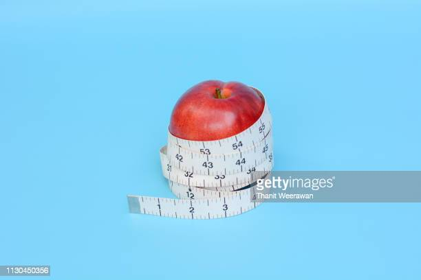 Red apple with white color measuring tape on blue background, Diet and healthy concept.