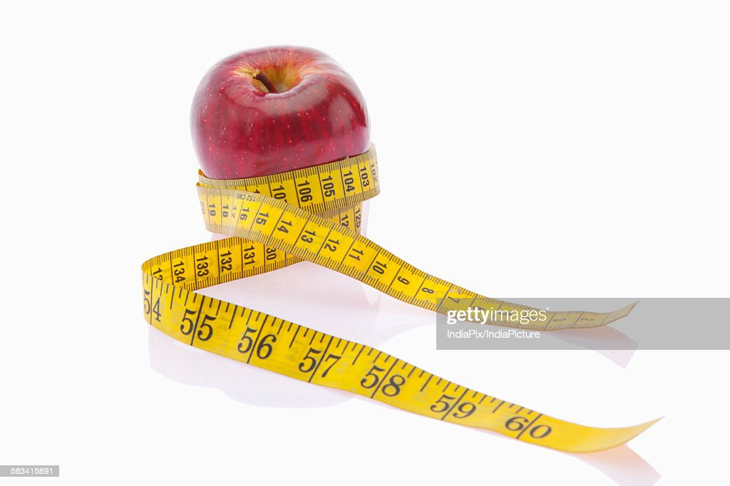 Red apple wrapped with measuring tape : Stock Photo