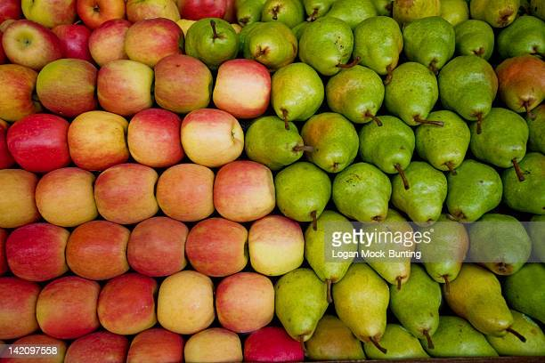 Red apples and green pears lay in a pile at a fruit stand in Maryland, USA.