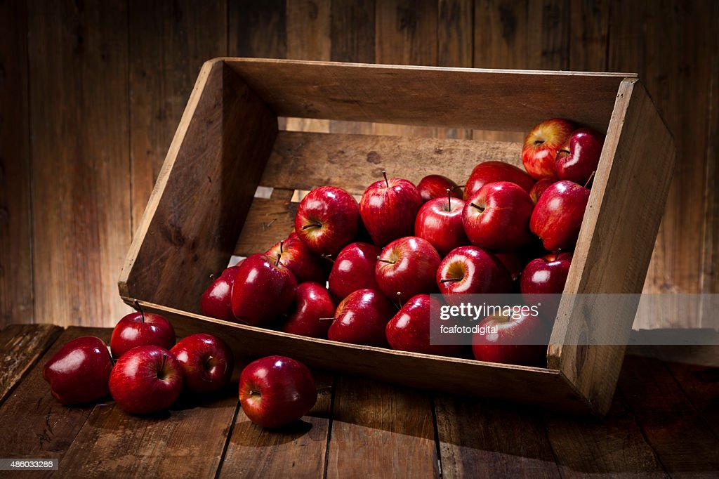 Red apples in a crate on rustic wood table : Stock Photo