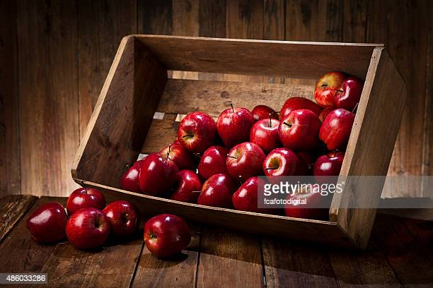 Red apples in a crate on rustic wood table