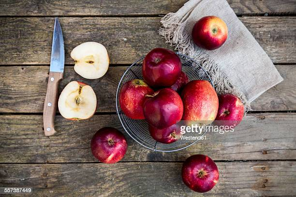 Red apples in basket on dark wood