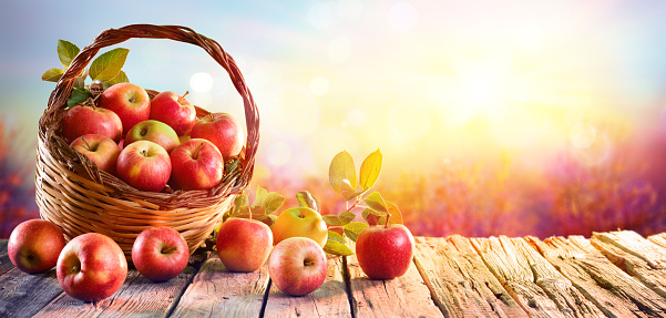Red Apples In Basket On Wooden Table At Sunset 1020706914