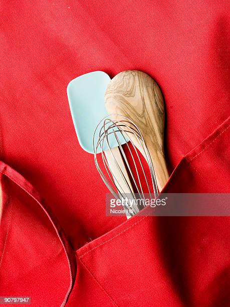 red apron with a spatula, a whisk and a wooden mixing spoon