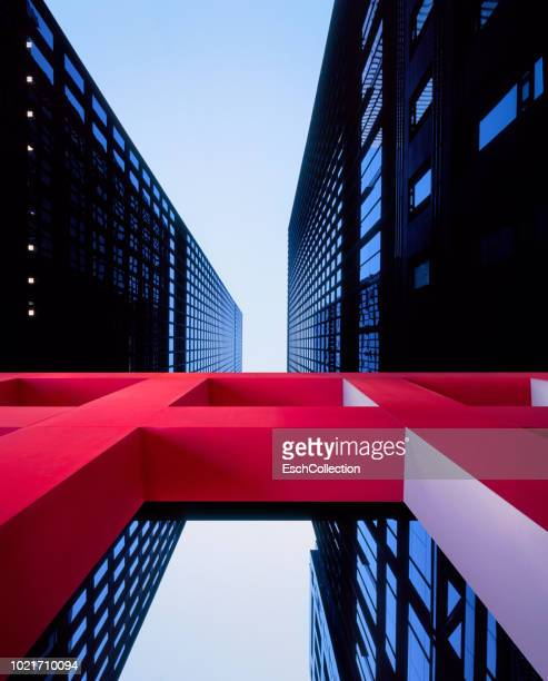 Red architectural sculpture in front of modern office buildings