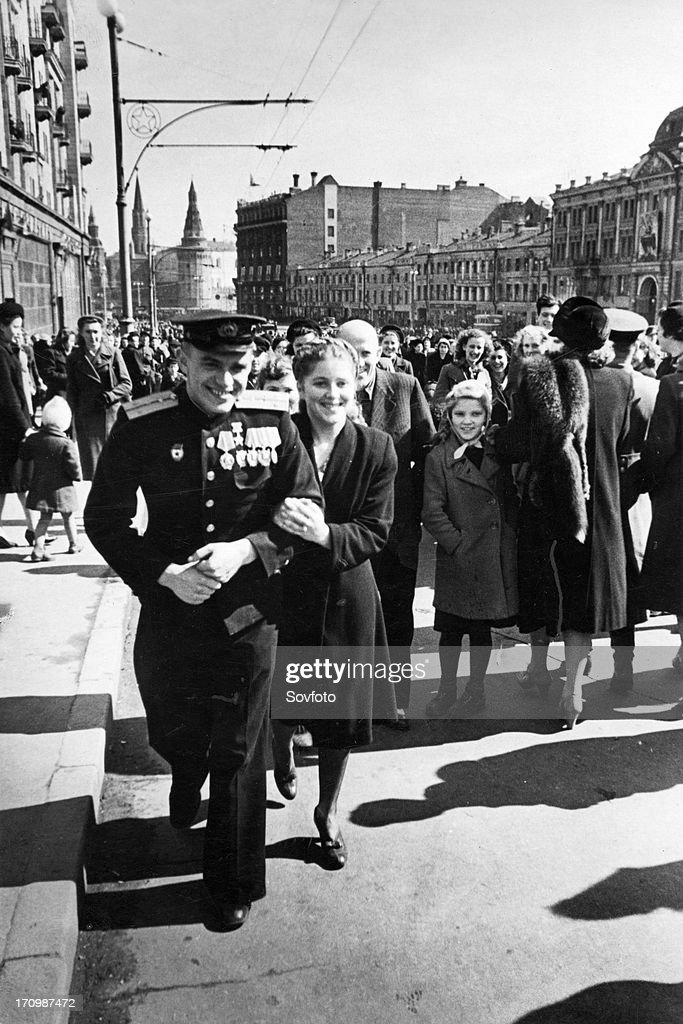 A red army soldier and his girlfriend on gorky street after the victory day celebrations in red square on may 9, 1945, the towers of the moscow kremlin can be seen in the background.
