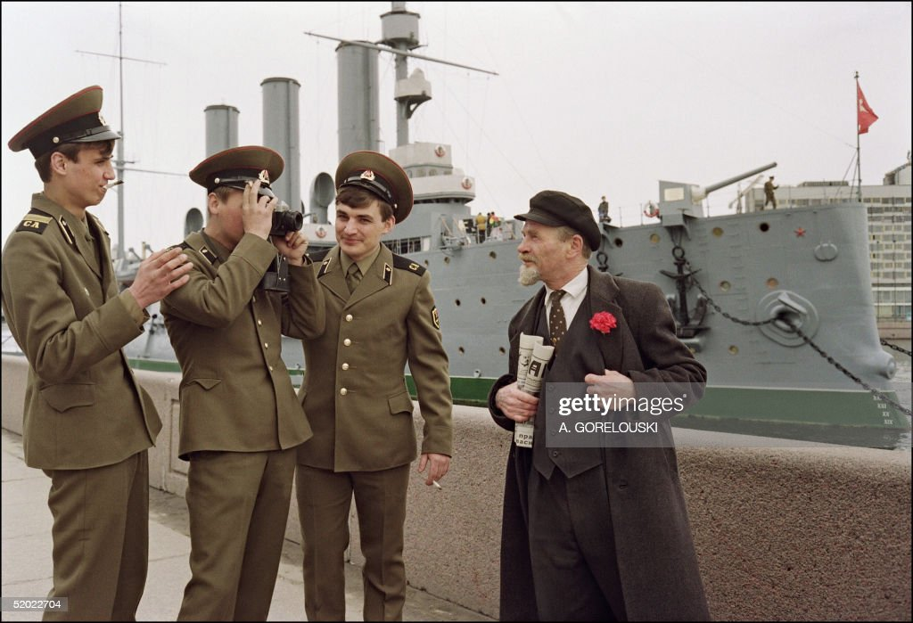 A Red Army soldier takes a picture of a Lenin look-alike (R) holding Russia's communist newspaper 'Pravda' while fellow soldiers joke in front of the cruiser Aurora anchored in the river Neva opposite the Winter Palace 03 May 1991 in Saint Petersburg. After the Aurora fired a single blank shell 26 October 1917 from Neva in Petrograd, and two shells fired from another battery struck the Winter Palace, the Bolshevik-led armed workers (Red Guards) overthrew the Provisional Government of Alexander Kerentsky based in the Winter Palace. The country's second revolution in eight months brought Vladimir Lenin and Leon Trotsky to power.