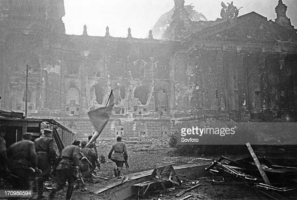 Red army soldiers carrying their battle standard storm the reichstag, berlin world war 2.