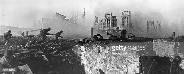 Red Army troops storming an apartment block amidst the ruins of war-torn Stalingrad during World War II. This is a composite image.