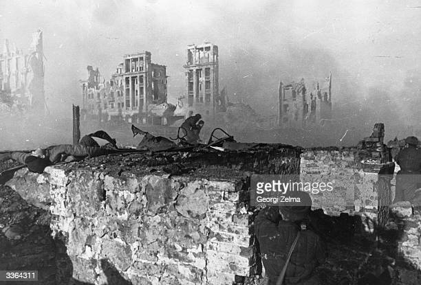 Red Army troops storming an apartment block amidst the ruins of wartorn Stalingrad during World War II